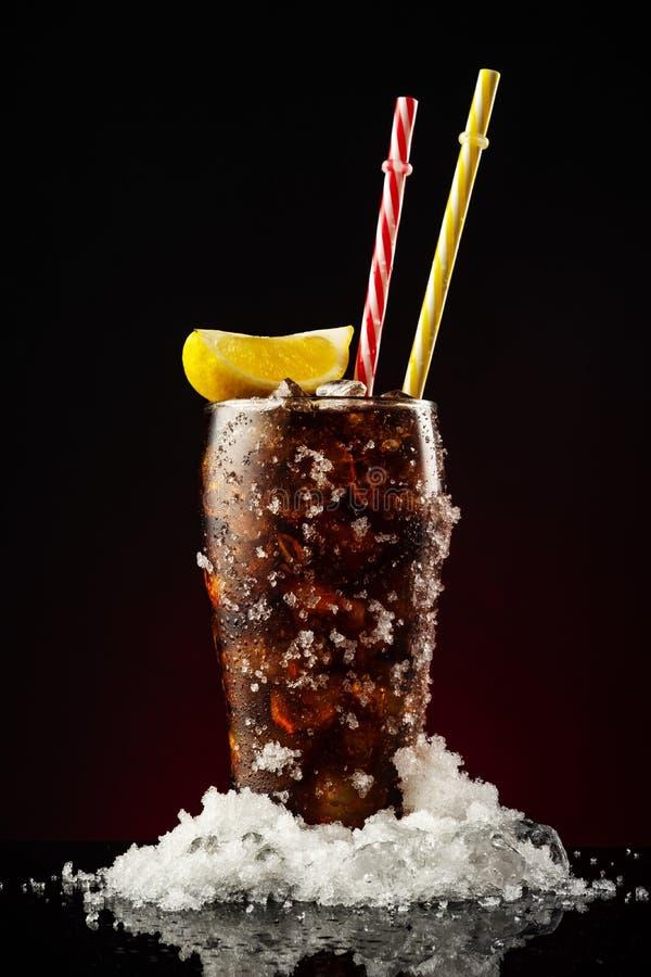 Cola de cristal con hielo y paja Vidrio frío de cola con el limón imágenes de archivo libres de regalías