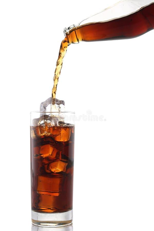 A cola de derramamento bebe da garrafa ao vidro com os cubos de gelo no branco foto de stock royalty free