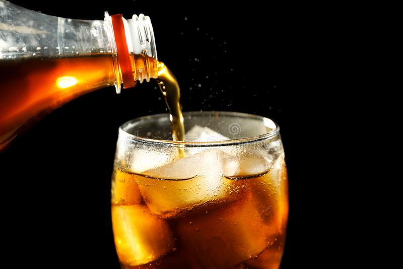 Cola de derramamento da garrafa no vidro com gelo imagem de stock royalty free