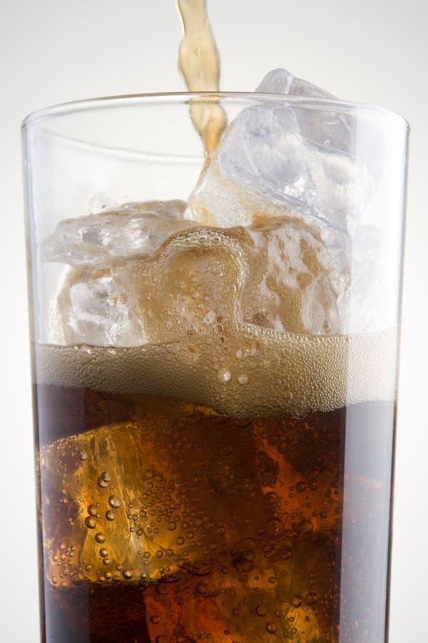 Cola de derramamento em um vidro do gelo foto de stock royalty free