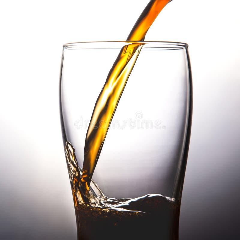 Cola de derramamento no vidro com gelo no espaço branco da cópia do fundo imagem de stock