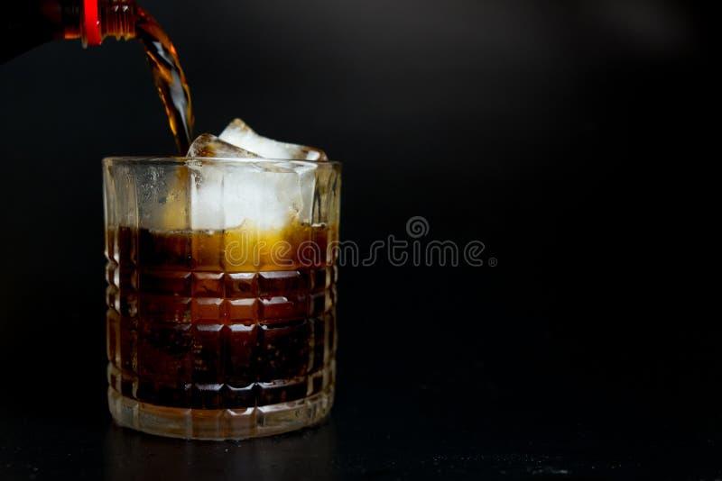 Cola de refrescamento de derramamento da garrafa no vidro com cubos de gelo imagens de stock