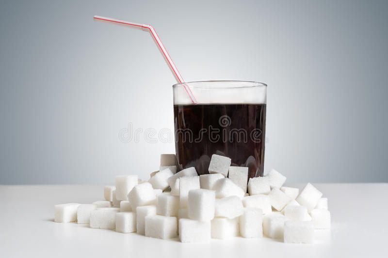 Cola drink in glass and many sugar cubes around. Unhealthy eating concept royalty free stock photos