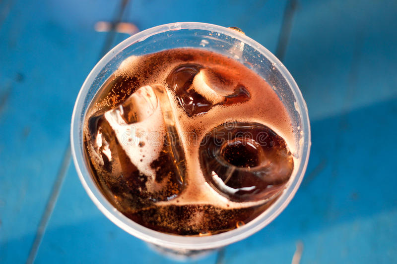 Cola drink and ice in glass with bubbles stock photo
