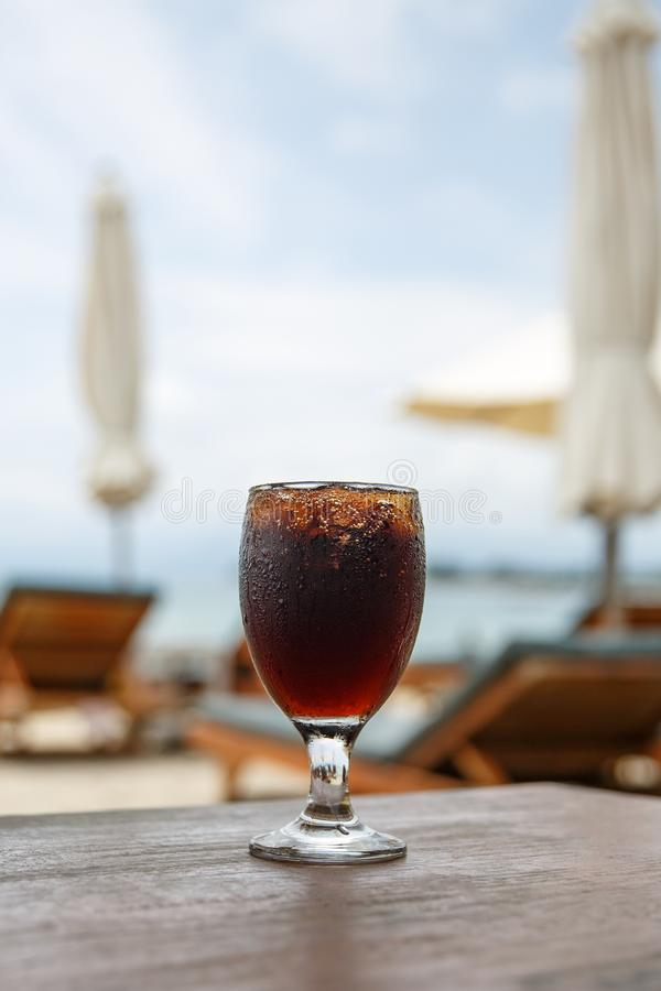 Cola glass on beach with umbrellas. Cooling drink royalty free stock images