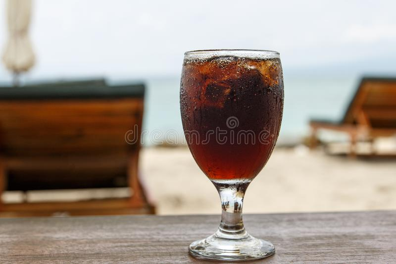 Cola glass on beach with umbrellas. Cooling drink royalty free stock photo