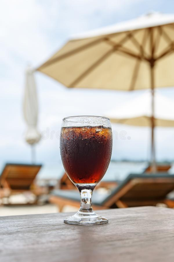 Cola glass on beach with umbrellas. Cooling drink stock photography