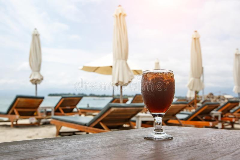 Cola glass on beach with umbrellas. Cooling drink stock photo
