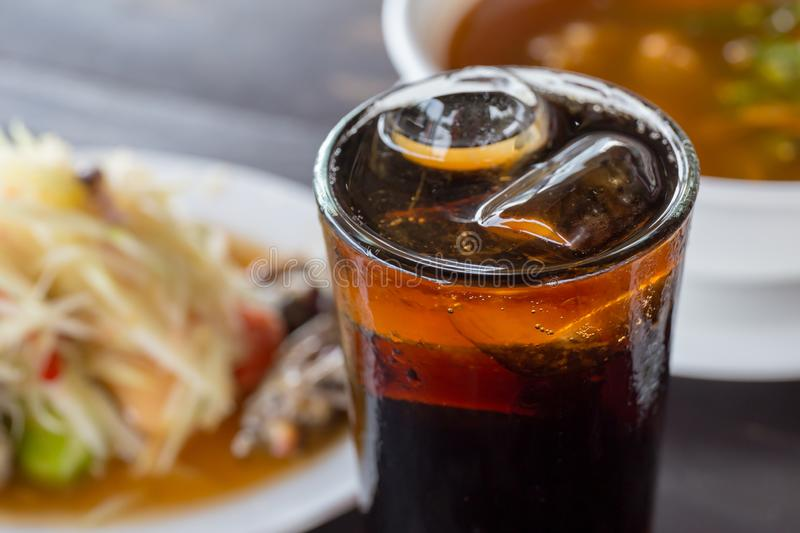 Cola in glass and ice cube on the food table. stock photography