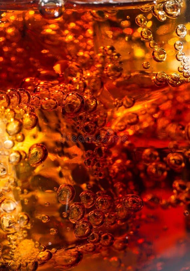 Cola i exponeringsglas med is och bubblor av gas royaltyfria foton