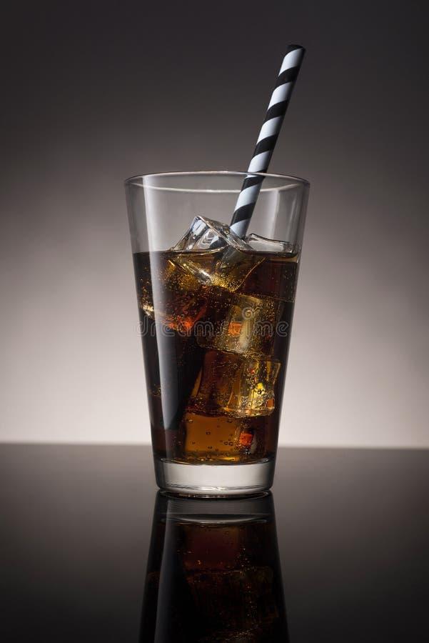Cola med rom och is i ett exponeringsglas med en randig tubule arkivfoto