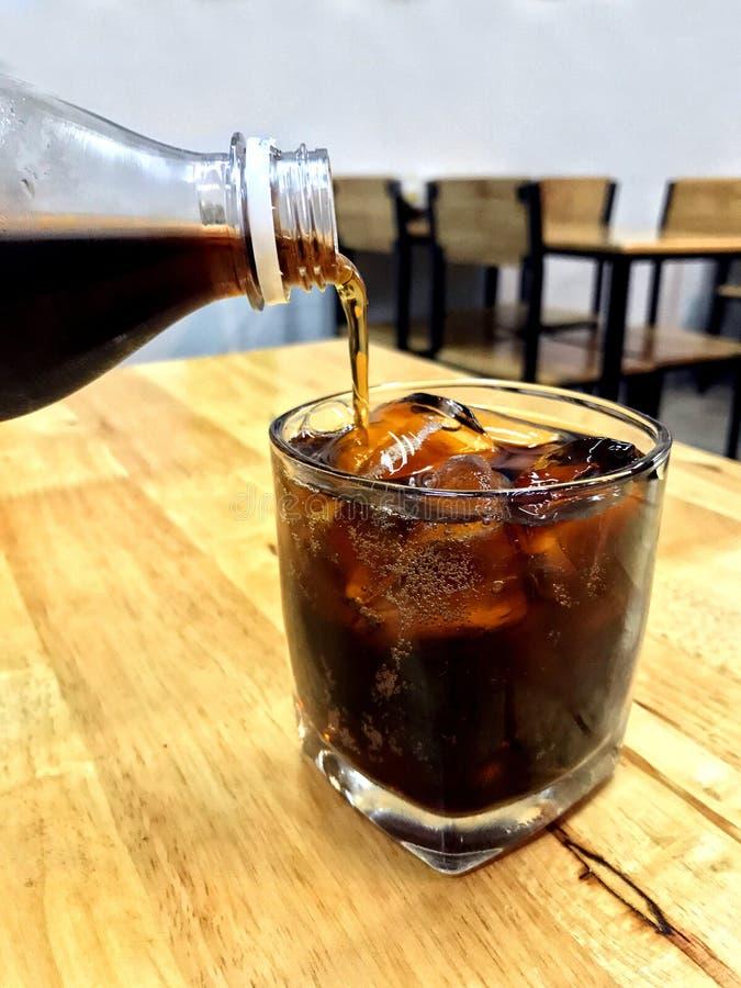 A cola no gelo de vidro, cola de derramamento das garrafas de vidro bebe a um vidro com cubos de gelo, cola na bebida de vidro do fotos de stock royalty free