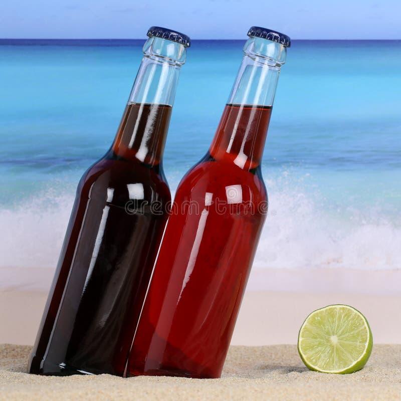 Cola- och lemonadläsk på stranden i sand arkivbild