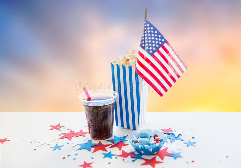 Cola and popcorn with candies on independence day. Independence day, celebration, patriotism and holidays concept - close up of american flag, cola cup, popcorn stock photos