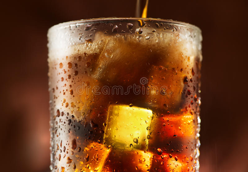 Cola pouring in glass with ice cubes stock photo