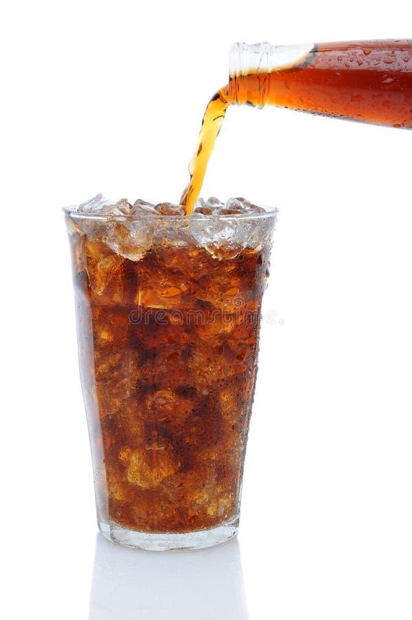 Cola que derrama do frasco no vidro do gelo fotos de stock