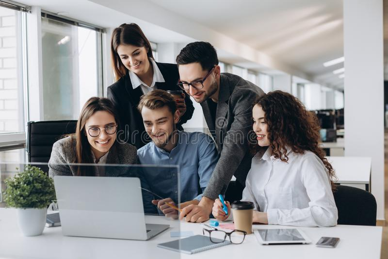 A colaboração é uma chave ao sucesso Executivos novos que discutem algo ao olhar o monitor do computador junto dentro imagem de stock royalty free