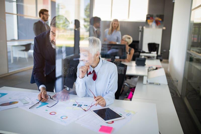 Colaboração e análise pelos executivos que trabalham no escritório foto de stock royalty free