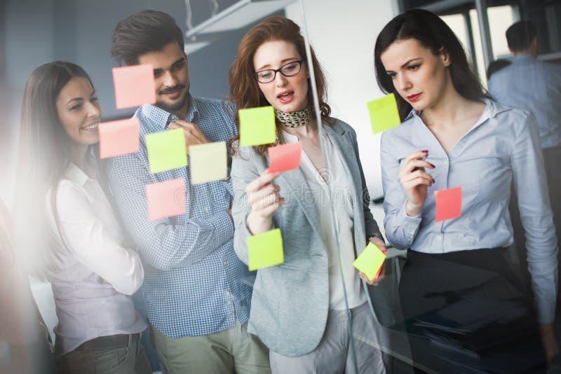 Colaboração e análise pelos executivos que trabalham no escritório imagens de stock