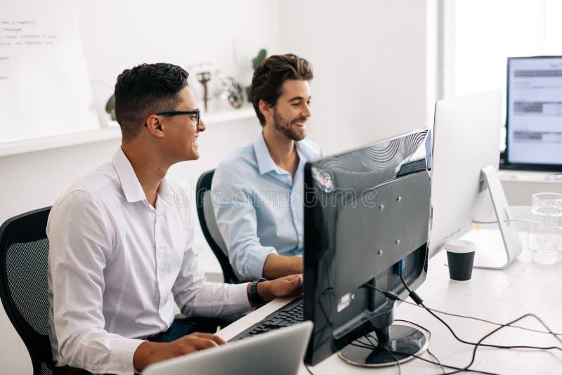 Colaboradores de aplicação que trabalham em computadores no escritório imagens de stock