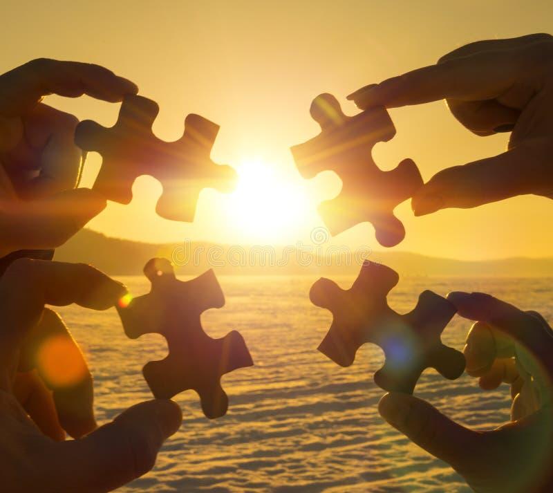 Colaboran cuatro manos que intentan conectar un pedazo del rompecabezas con un fondo de la puesta del sol imagenes de archivo