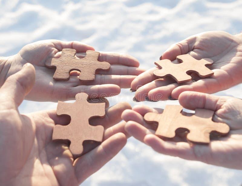 Colaboran cuatro manos que intentan conectar un pedazo del rompecabezas con un fondo de la puesta del sol foto de archivo libre de regalías
