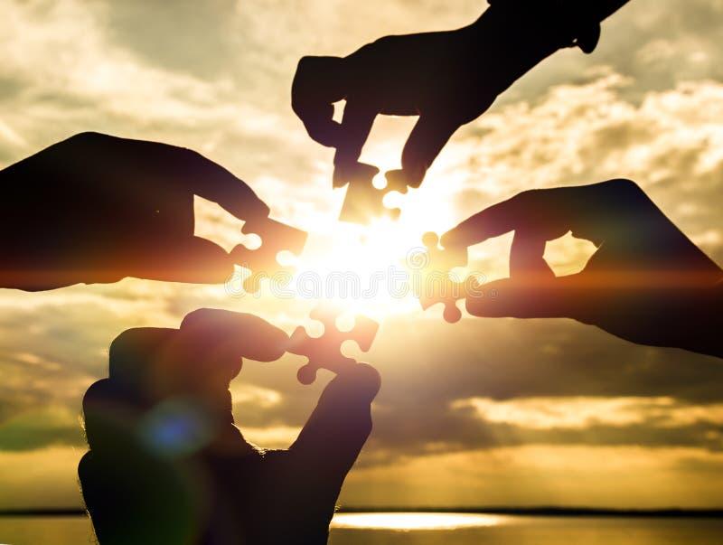 Colaboran cuatro manos que intentan conectar un pedazo del rompecabezas con un fondo de la puesta del sol imagen de archivo