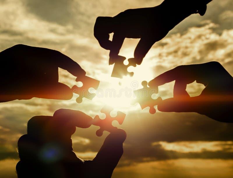 Colaboran cuatro manos que intentan conectar un pedazo del rompecabezas con un fondo de la puesta del sol fotos de archivo