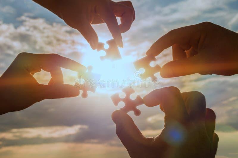 Colaboran cuatro manos que intentan conectar un pedazo del rompecabezas con un fondo de la puesta del sol imagen de archivo libre de regalías