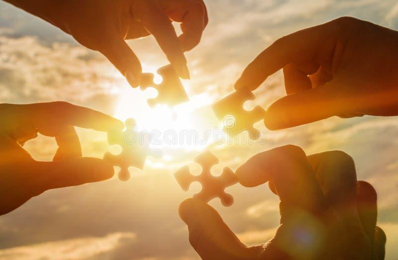 Colaboran cuatro manos que intentan conectar un pedazo del rompecabezas con un fondo de la puesta del sol Un rompecabezas a dispo imágenes de archivo libres de regalías