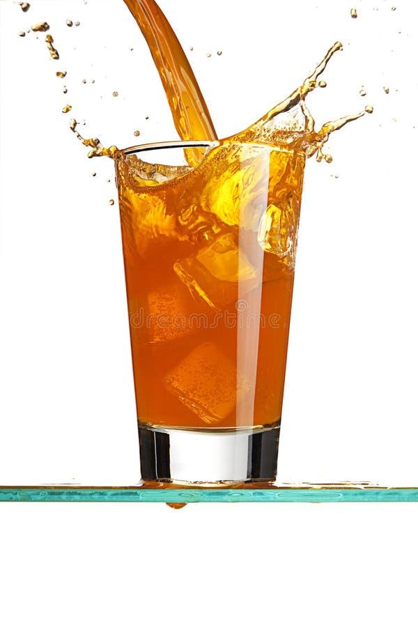 Colada de una bebida anaranjada fotos de archivo
