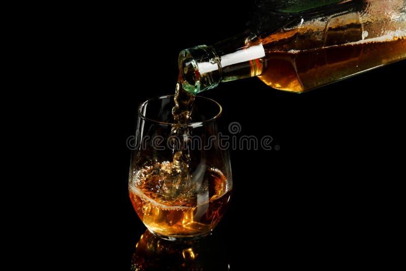 Colada del whisky de la botella en el vidrio en fondo negro fotos de archivo libres de regalías