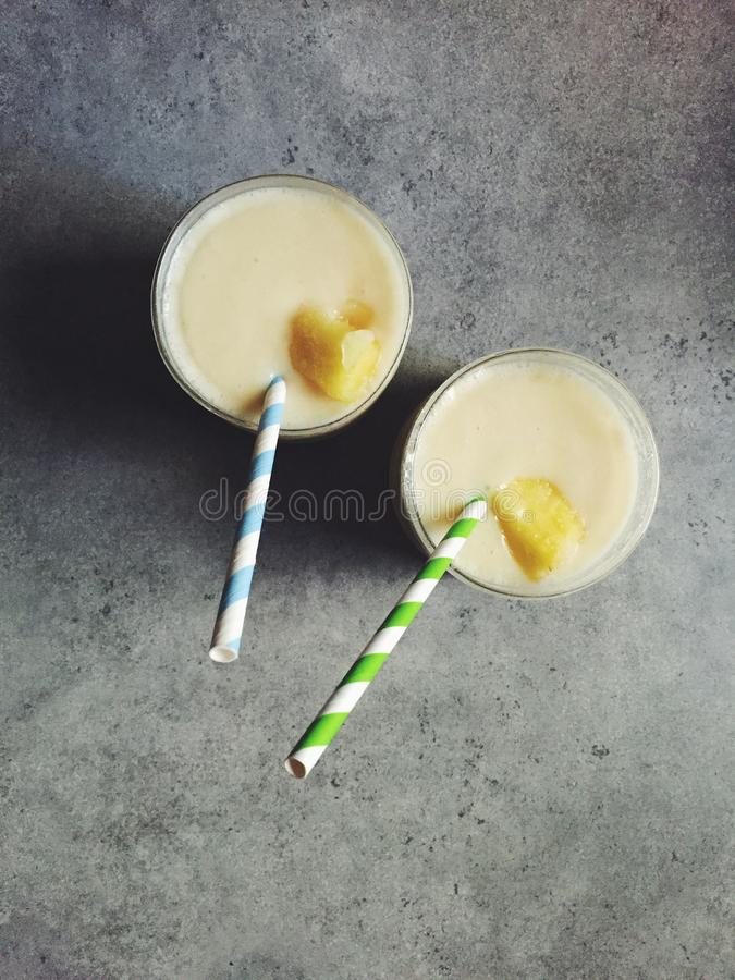 Colada fait maison de piña en deux verres avec des pailles de papier rayé photographie stock libre de droits