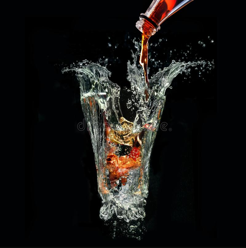 Coladrink med is som blandar in i imaginärt exponeringsglas ut ur vattenfärgstänk på svart bakgrund royaltyfri fotografi