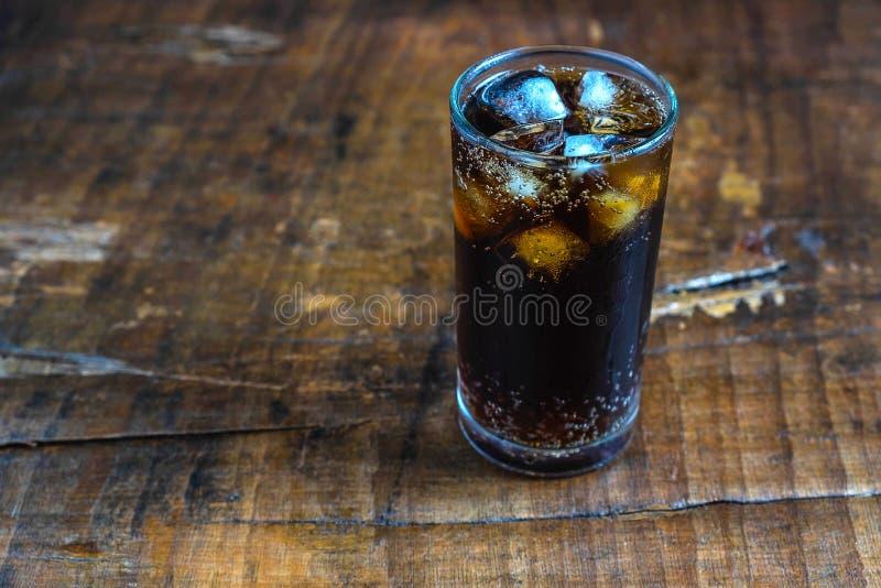 Coladrink, svarta läsk i ett exponeringsglas på tabellen royaltyfria foton