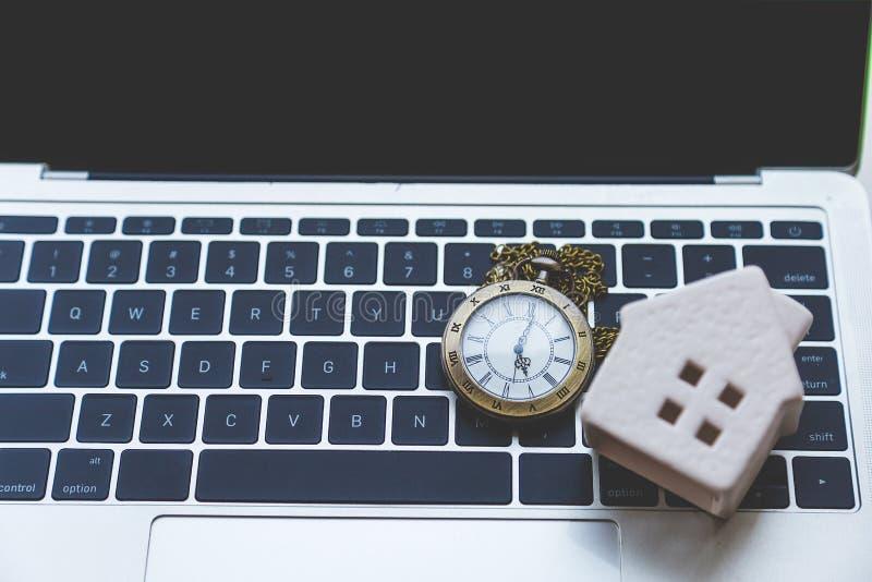 Colar bonita do relógio no portátil com a casa cerâmica na tabela branca imagens de stock royalty free