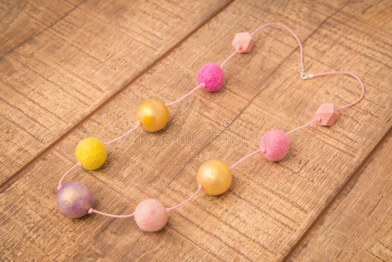 Colar colorida dos grânulos de feltro da madeira redonda e das lãs feito a mão com os grânulos cor-de-rosa, dourados e amarelos d imagem de stock royalty free