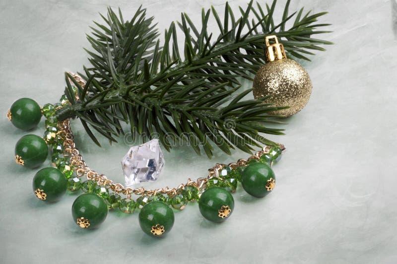 Colar com pedras verdes em um ramo de uma árvore de Natal com uma bola em um fundo abstrato fotografia de stock