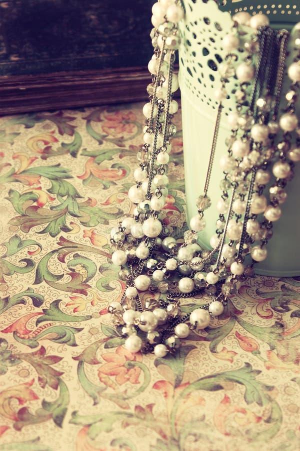 Colar da pérola do vintage sobre o fundo floral do teste padrão filtro retro imagens de stock royalty free