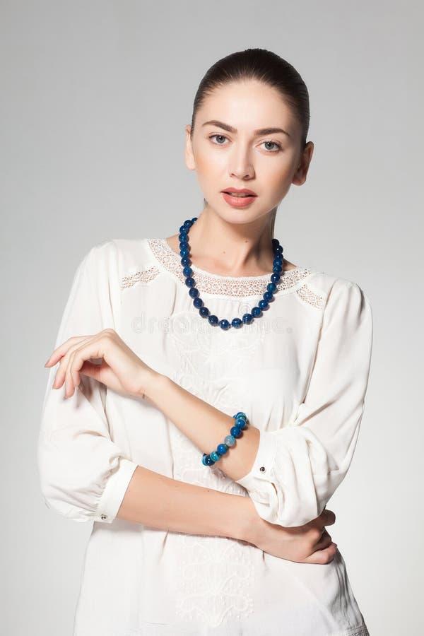 Colar de mármore vestindo da mulher bonita no fundo cinzento fotografia de stock