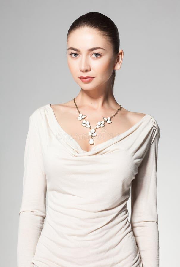 Colar de mármore vestindo da mulher bonita no fundo cinzento fotos de stock