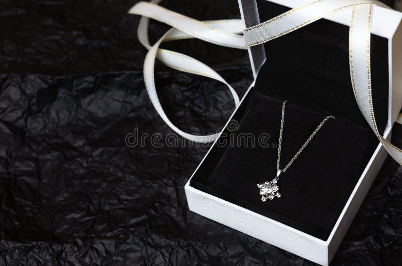 Colar de prata na caixa de presente no fundo preto imagem de stock royalty free