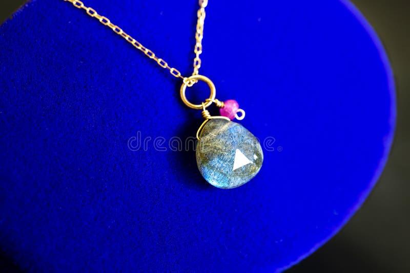 Colar dourada com labradorite com o rubi pequeno na caixa azul da joia fotografia de stock royalty free
