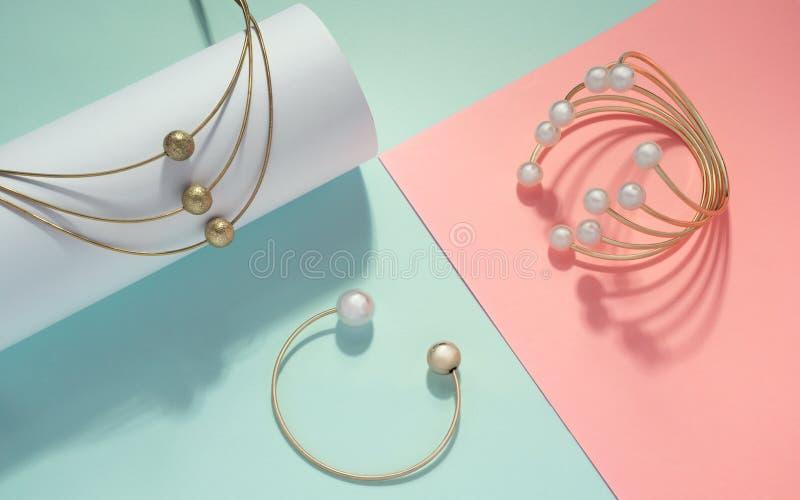 Colar e braceletes dourados com as pérolas no fundo das cores pastel imagem de stock