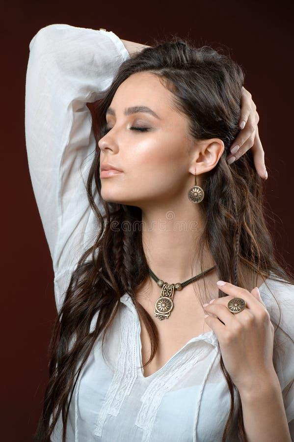 Colar e brinco na jovem mulher Modelo bonito com cabelo longo perfeito imagens de stock