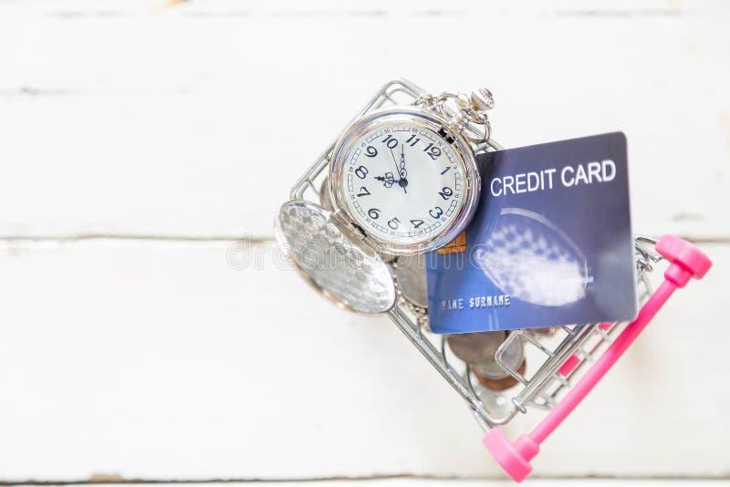 Colar e moeda de prata bonitas do relógio com os cartões de crédito no mini carrinho de compras no assoalho de madeira branco fotografia de stock royalty free