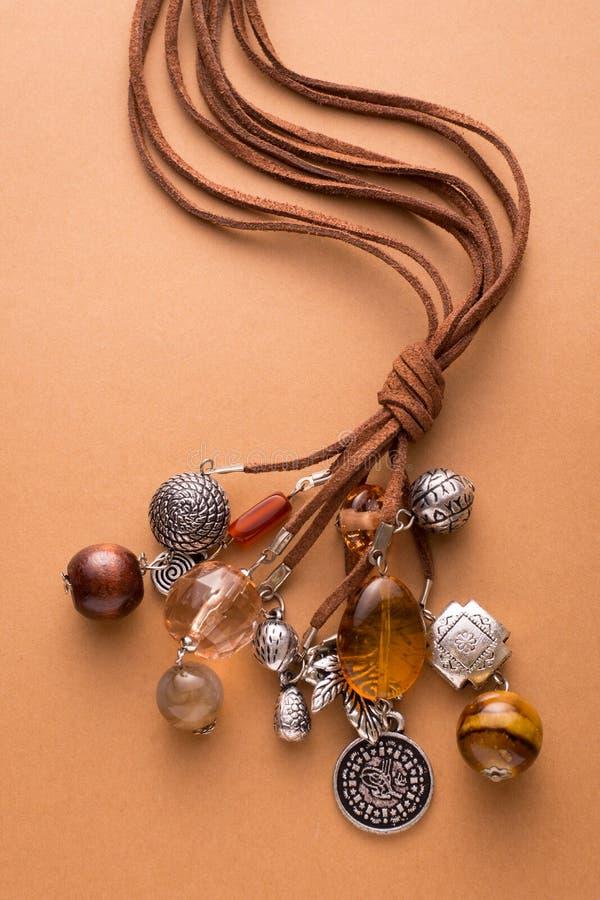 Colar feita com encantos do couro e da prata de Brown fotos de stock royalty free