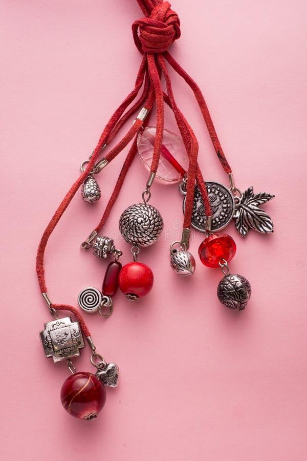 Colar feita com encantos vermelhos do couro e da prata imagem de stock