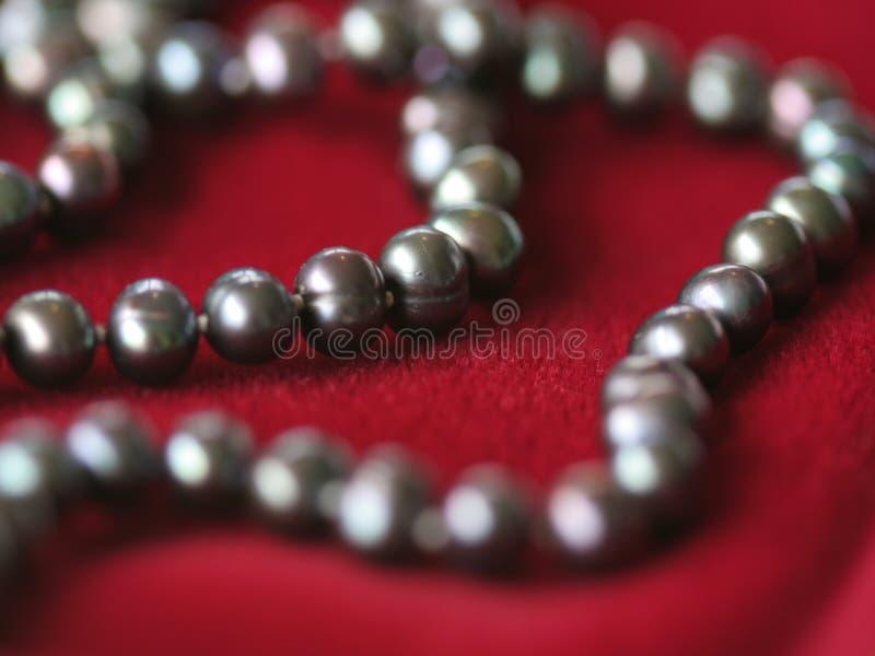 Colar preta da pérola em velvet2 vermelho fotografia de stock royalty free