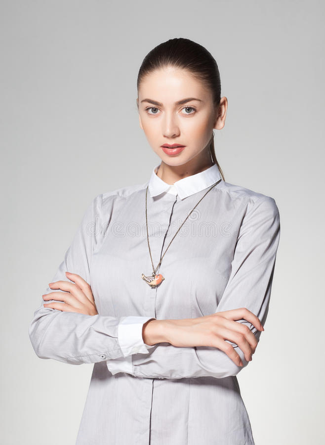 Colar vestindo da mulher bonita no fundo cinzento imagem de stock